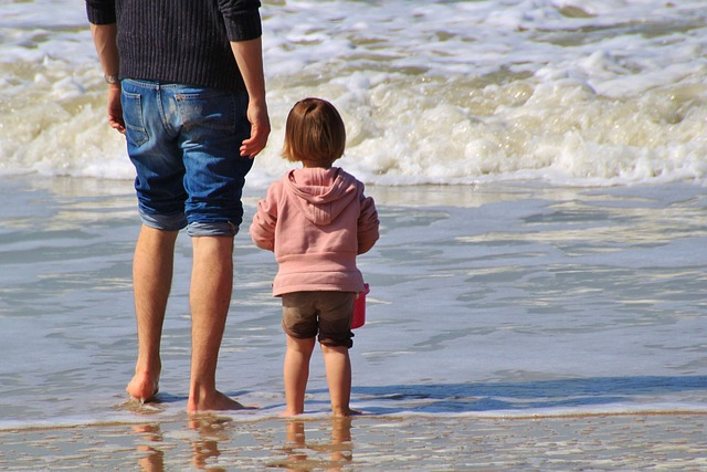 Parent and Daughter wading in ocean